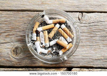 Cigarette Butts With Ash In Ashtray On Grey Wooden Table