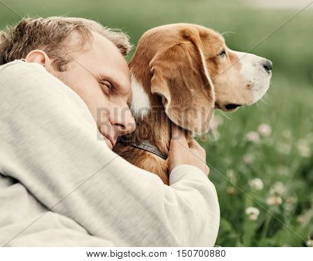 Man hugs his favorite dog, who's quite indifferent