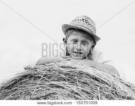 Boy in straw hat lying on the haystack BW