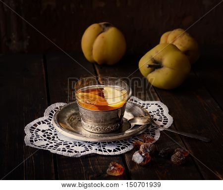 tea with quince, quince fruit, original napkin and a teaspoon on the wooden background