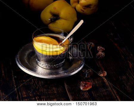 tea with quince, quince fruit, sugar, a teaspoon on the wooden background