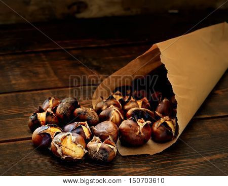 roasted chestnuts in paper bags on a wooden background