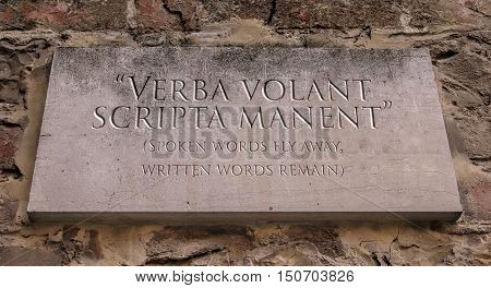Verba volant scripta manent. Latin phrase meaning Spoken words fly away, written words remain. Engraved text.