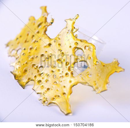 A piece of cannabis oil concentrate aka shatter with glass rig isolated against white background