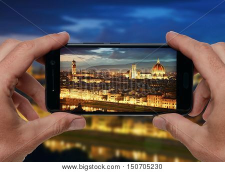 Travel concept. Hands making photo of night city with smartphone camera. Florence, Italy.