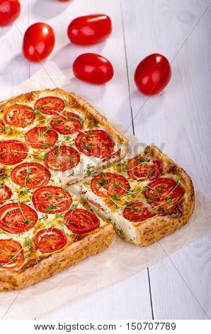 Tart with tomato and fresh herbs on a white wooden table. Healthy eating Vegetable Pie.