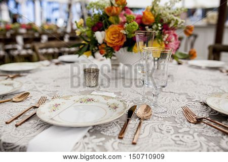 table set for wedding reception with antique dishes