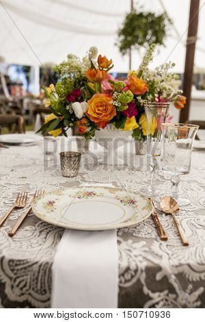 setup for wedding reception with antique plates and stemware