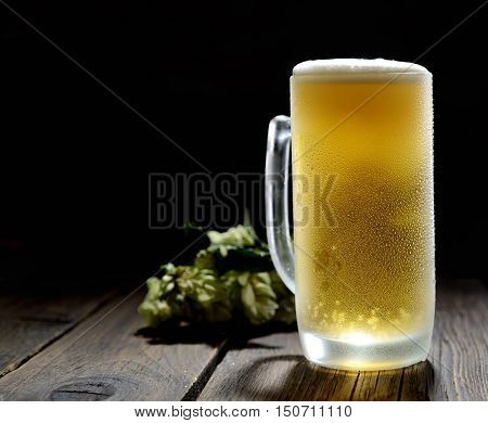 cold frothy beer in a glass and hop on a gray wooden background