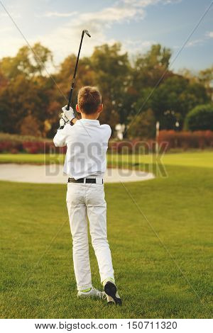 Boy golf player playing golf at evening, back view