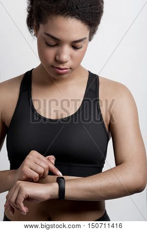 Young athletic woman checking fitness tracker  in studio