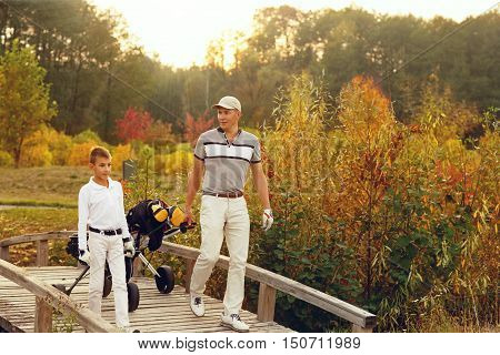 Father with son golfers are walking enjoying autumn lanscape