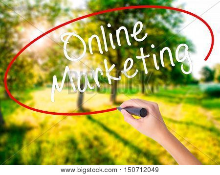 Woman Hand Writing Online Marketing With A Marker Over Transparent Board