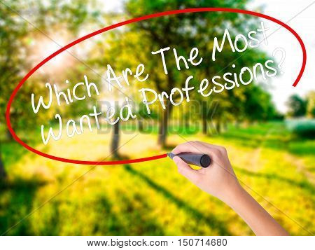Woman Hand Writing Which Are The Most Wanted Professions? With A Marker Over Transparent Board