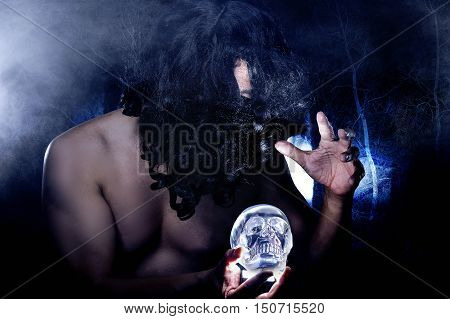 Primitive looking man in a dark smoky forest as a witch doctor or shaman