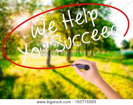 Woman Hand Writing We Help You Succeed With A Marker Over Transparent Board