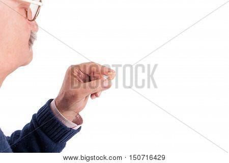 Senior man showing his hearing aid. Studio shot isolated on white background.