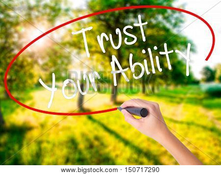 Woman Hand Writing Trust Your Ability  With A Marker Over Transparent Board
