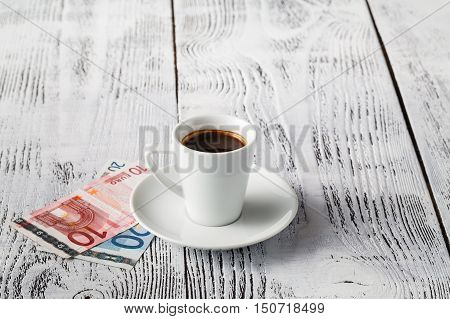euro bill and cup of coffee on wooden table. Payment tip.