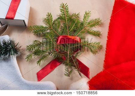 Christmas tree with red ribbon on wooden background, Christmas sock, red hat, gift , happy holidays
