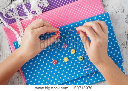 hand holds needle sews a button on cloth