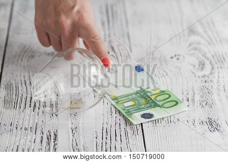 Empty glass and one hundred Euro banknotes on wooden table