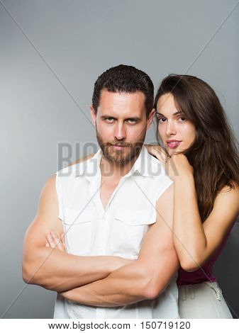 Couple of handsome bearded man in white shirt and sexy woman in pink blouse that rested on his shoulder on gray studio background