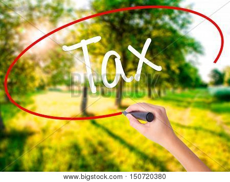 Woman Hand Writing Tax With A Marker Over Transparent Board