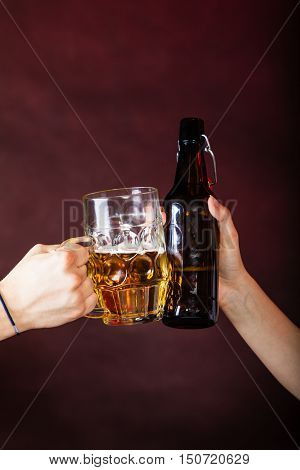 Drinking alcohol liquor party relax celebration concept. Closeup of beer toast. Two people colliding stein and ale bottle.