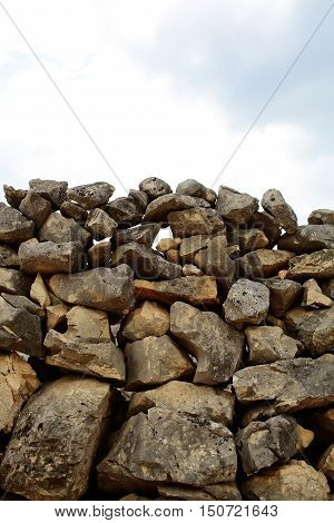 Wall of natural stone rock high fence rustic masonry construction copy space on sky background