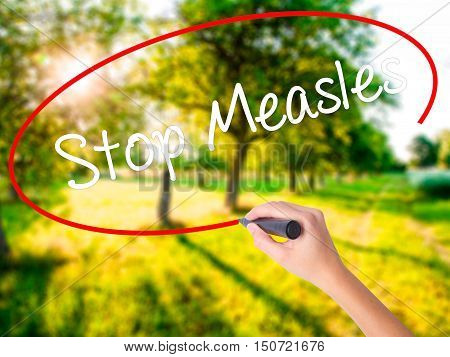 Woman Hand Writing Stop Measles  With A Marker Over Transparent Board