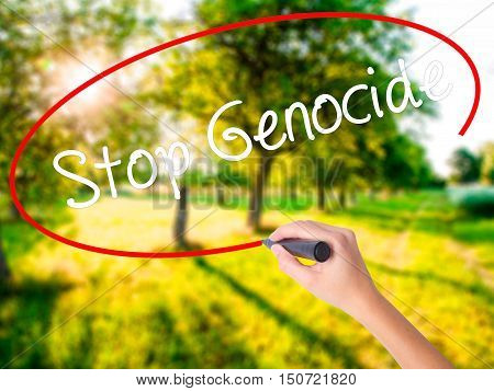 Woman Hand Writing Stop Genocide With A Marker Over Transparent Board .