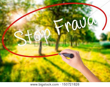 Woman Hand Writing  Stop Fraud  With A Marker Over Transparent Board