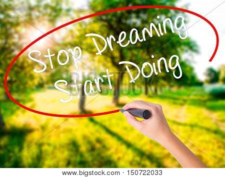 Woman Hand Writing Stop Dreaming Start Doing  With A Marker Over Transparent Board