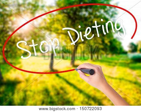 Woman Hand Writing Stop Dieting With A Marker Over Transparent Board .