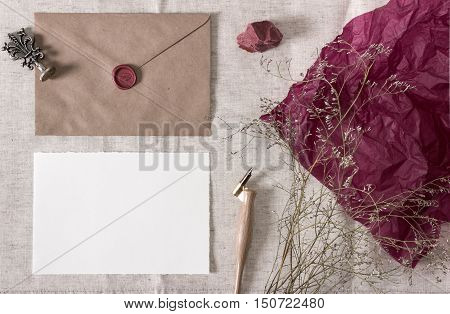 Mockup with envelope wax seal nib pen blank card and dry flowers. Wedding calligraphy vintage stationary Mock-up top view.
