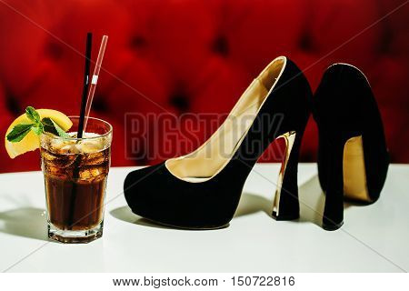 Black ladys shoes and nonalcoholic cocktail with lemon and mint in glass with transparent and black rolls on white table on red background