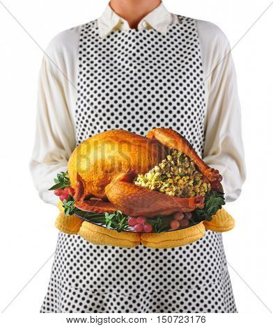 Closeup of a homemaker in an apron and oven mitts holding a platter with a roasted turkey.  Woman is unrecognizable. Shallow depth of field over white..