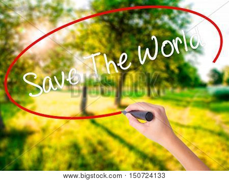 Woman Hand Writing Save The World With A Marker Over Transparent Board .