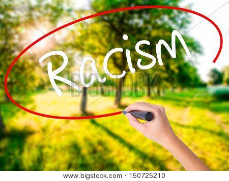 Woman Hand Writing Racism With A Marker Over Transparent Board .
