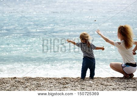 Mother young woman and son baby boy sit on pebble beach near blue sea windy weather on natural background copy space