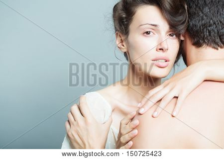 Couple of sensitive pretty woman with collected hair embracing man standing back to camera and compress her shoulder on gray studio background copy space