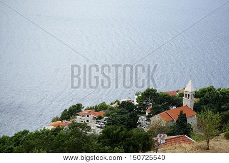 Mountain village with houses and villas with terracotta tiled roofs with green trees on coast of beautiful blue sea