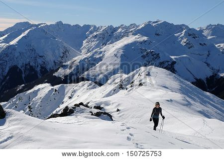 A Woman Hiker Climbs a Snowy Mountain on a Sunny Day.  Mt Bealey, Arthurs Pass, Southern Alps, Canterbury, New Zealand.