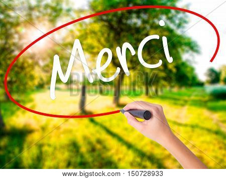 Woman Hand Writing Merci  (thank You In French) With A Marker Over Transparent Board .