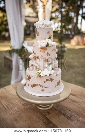 Four tiered wedding cake with white roses at outdoor reception