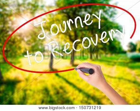 Woman Hand Writing Journey To Recovery With A Marker Over Transparent Board