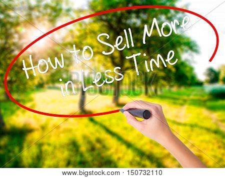 Woman Hand Writing How To Sell More In Less Time With A Marker Over Transparent Board .
