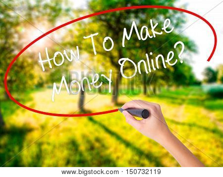 Woman Hand Writing How To Make Money Online? With A Marker Over Transparent Board