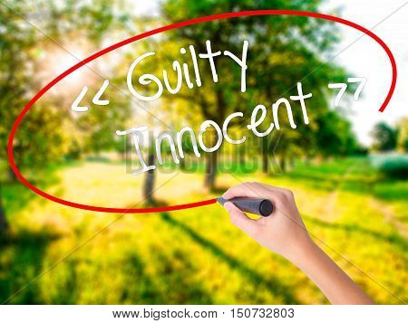 Woman Hand Writing Guilty - Innocent With A Marker Over Transparent Board .
